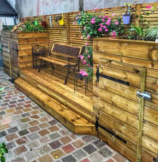 Caches pour cuve à eau en bois avec estrade, bacs à fleurs et décoration dans un jardin de ville au Guilvinec